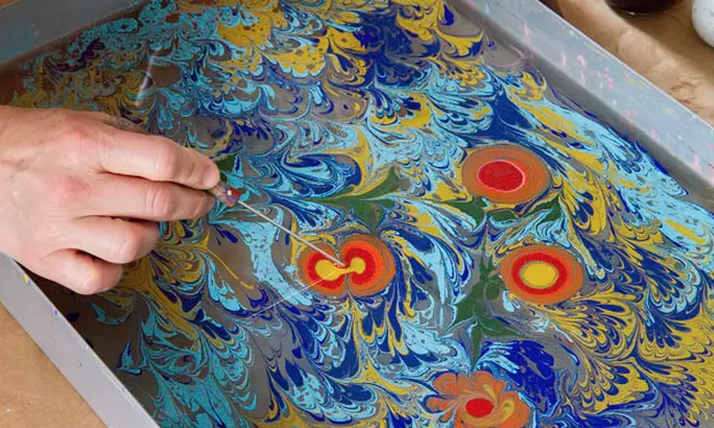 Image of a person marbled ink for paper design
