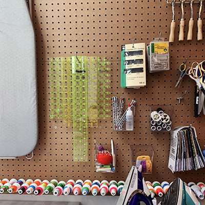 image of peg board with various sewing accessories hanging from it